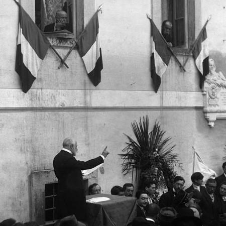 Oratore che si rivolge ad un uditorio, lapide in memoria di Enrico Ricci 1911